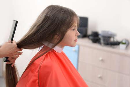 Klein meisje in een kapsalon Stockfoto