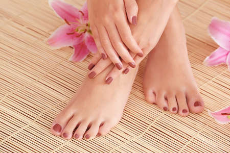 Female feet and hands with brown manicure on bamboo mat background 스톡 콘텐츠