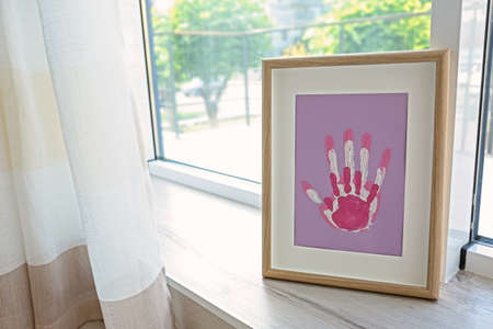 Family hand prints in frame on windowsill Stockfoto