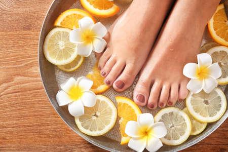 柑橘類の果物とスパボウルの女性の足、クローズアップ