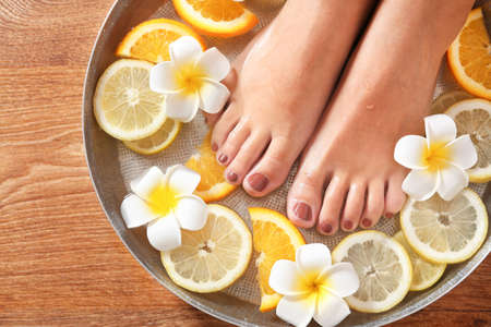 Female feet in spa bowl with citrus fruits, closeup