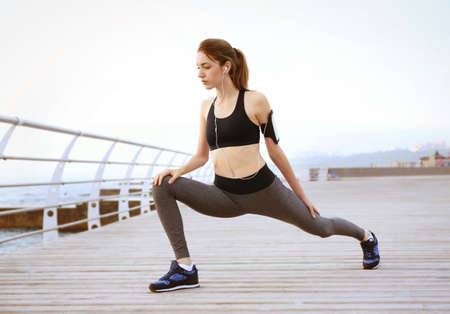 Young woman doing exercises on pier Stock Photo