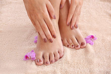 Female feet and hands with brown manicure and orchid on fabric background