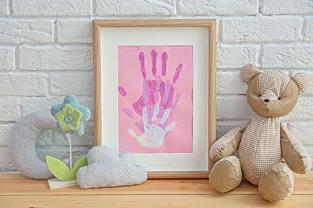 Family hand prints in frame and decor on table