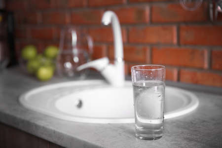 Glass of water and white sink at kitchen