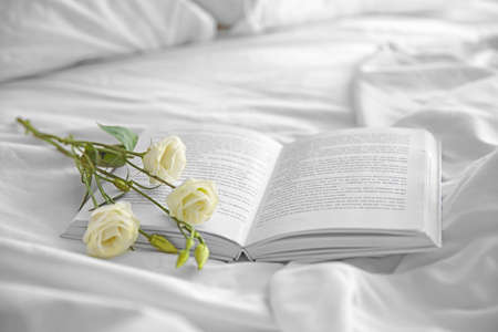 Opened book and beautiful flower on crumpled bed 版權商用圖片