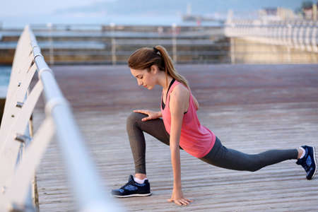Young woman doing exercises on pier Archivio Fotografico