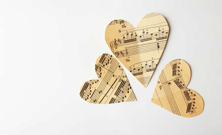 Paper hearts with notes on white background, music concept