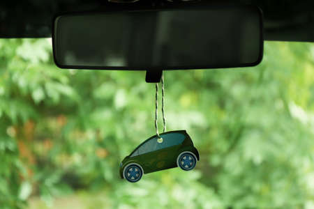 Air freshener hanging in the car on green natural background 스톡 콘텐츠