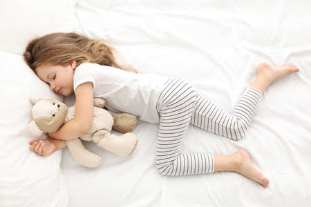 Cute little girl sleeping with teddy bear in bed Standard-Bild