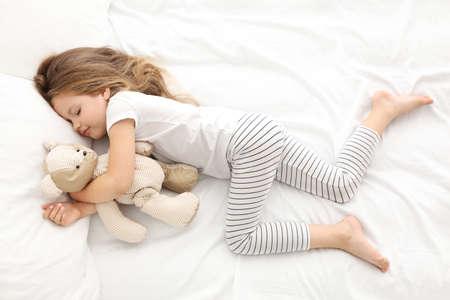 Niña linda que duerme con el oso de peluche en la cama Foto de archivo - 96568762