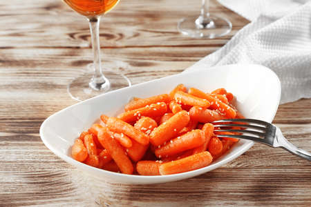 Cooked baby carrots with sesame in white plate on wooden background