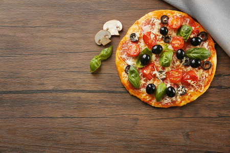 Tasty pizza with vegetables, herbs on wooden background Stockfoto
