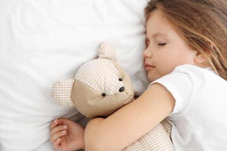Cute little girl sleeping with teddy bear in bed Stock fotó