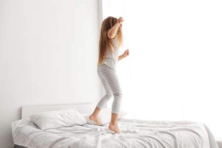 Cute little girl jumping on white bed Archivio Fotografico