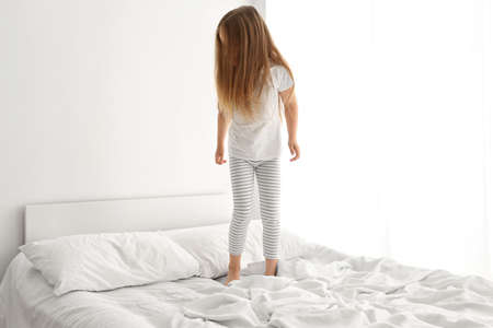 Adorable little girl having fun on white bed Stock Photo