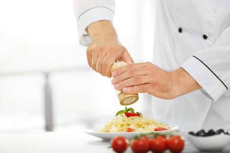 Chef preparing delicious pasta in kitchen Stock Photo