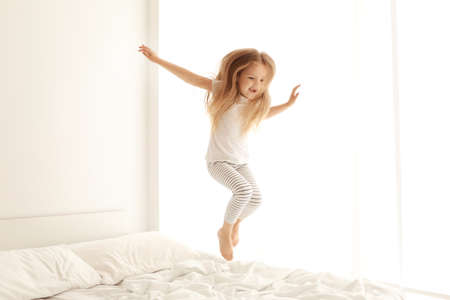 Cute little girl jumping on white bed Banque d'images