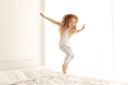 Cute little girl jumping on white bed Foto de archivo