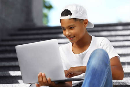 African American boy with laptop on staircases Stock Photo