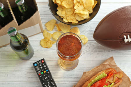 Glass of beer, bottles, snack and TV remote control on wooden background