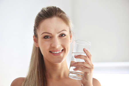 Beautiful girl drinking water on light background Standard-Bild