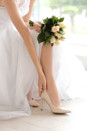 Bride in a beautiful wedding dress with bouquet of flowers putting on shoes Stock Photo