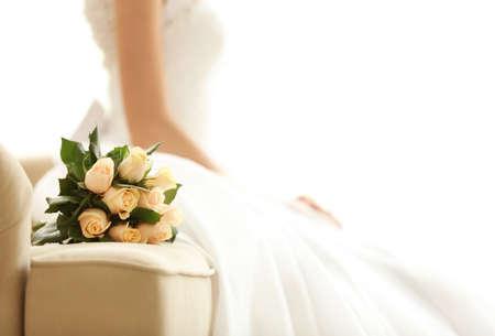 Bride in beautiful dress with wedding bouquet sitting on sofa 版權商用圖片 - 96096149
