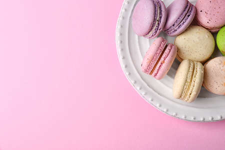 Tasty colorful macaroons in white plate on pink background