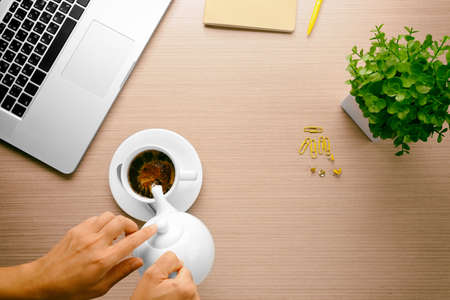 Woman hands pouring coffee into cup on office table Stock Photo