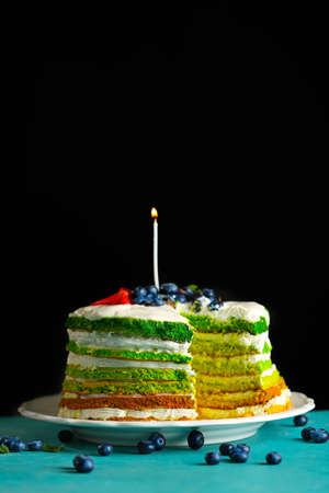 Delicious cake with candle on dark background