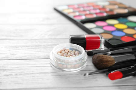 Professional make-up accessories on wooden table Imagens