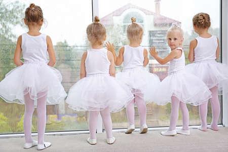 Cute girls standing near window in ballet class Stock Photo