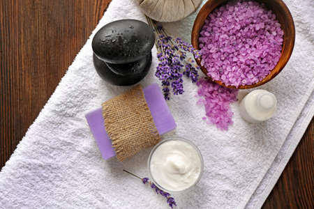 Spa composition with lavender, towel and cream on wooden background