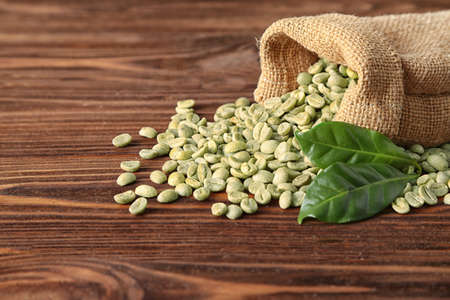 Coffee grains with green leaf in sackcloth on wooden table Imagens