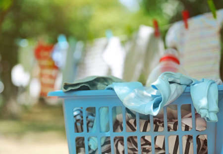 Blue plastic basket with baby laundry on blurred clothesline background