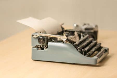 Retro typewriter on wooden table, blurred background