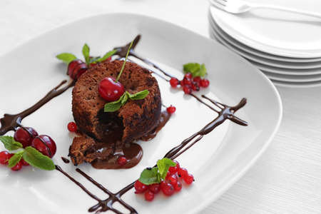 Delicious fondant with cherry and red currant on plate, closeup Stock Photo