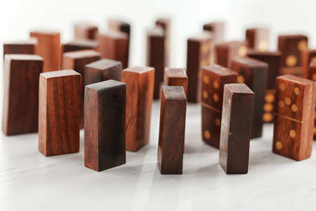 Circle of dominoes standing on light wooden background Stock Photo