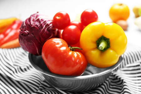 Bowl with fresh vegetables on napkin Stock Photo