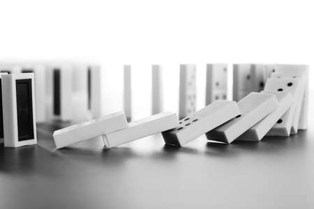 Dominoes falling on gray background