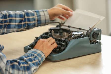 Man working on retro typewriter at desk