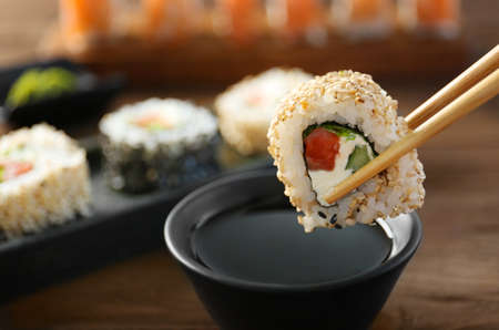 Tasty sushi roll with wooden chopsticks and sauce in bowl Stock Photo