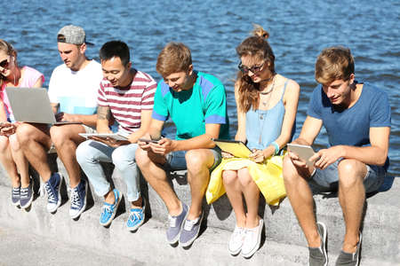 Young people with gadgets hanging out Stock Photo