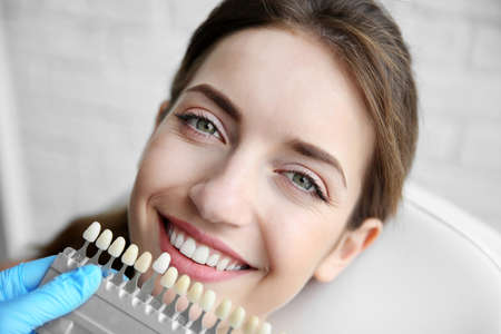 Young woman choosing color of teeth at dentist