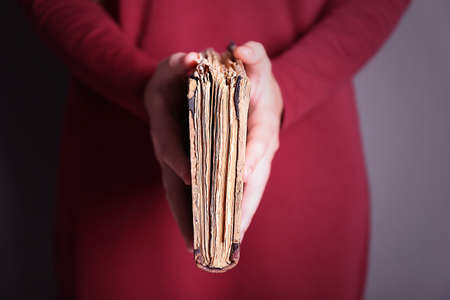 Woman holding old book on color background