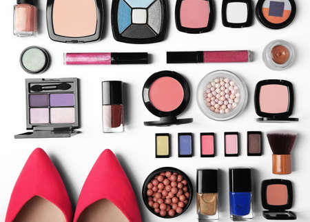 Makeup products, brushes and female shoes on a white background