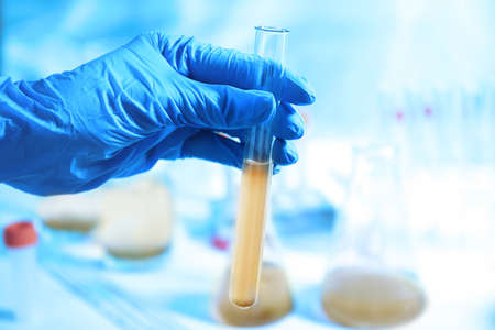Hand in glove holding test tube with contaminated water in laboratory closeup