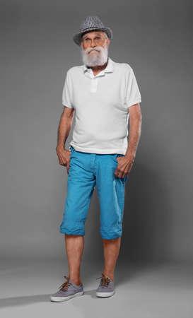 Elderly man in  stylish clothes on grey background 免版税图像