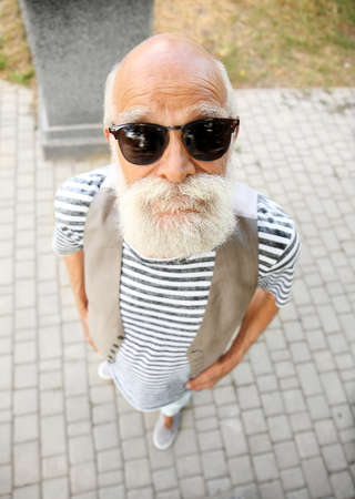 Elderly bearded man in stylish clothes at park